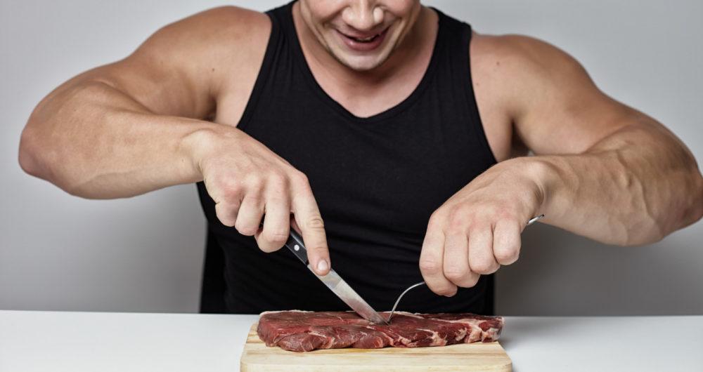 脂肪の多い肉を食べる男性